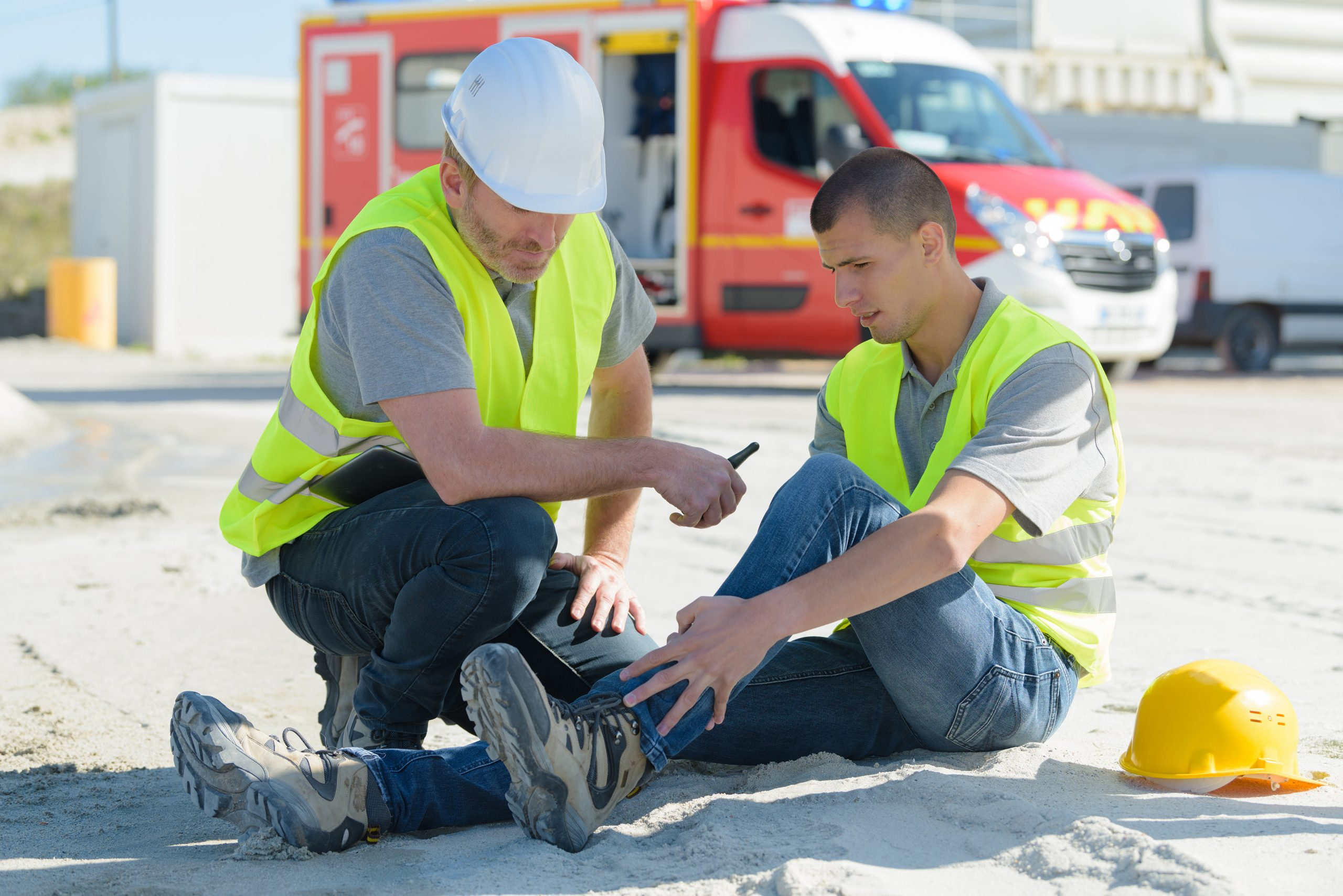 young construction worker on site with injured ankle